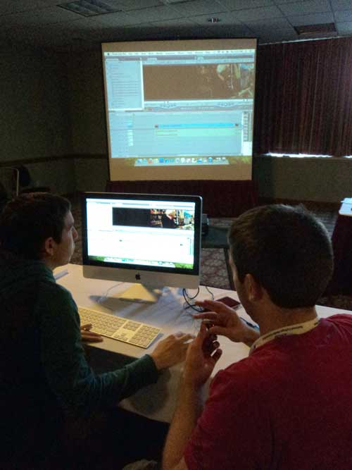 Rene Armendariz, New Mexico State University, (left) and Brandon Goodwin, University of Kentucky, edit video in Final Cut as their edit session is projected on screen.